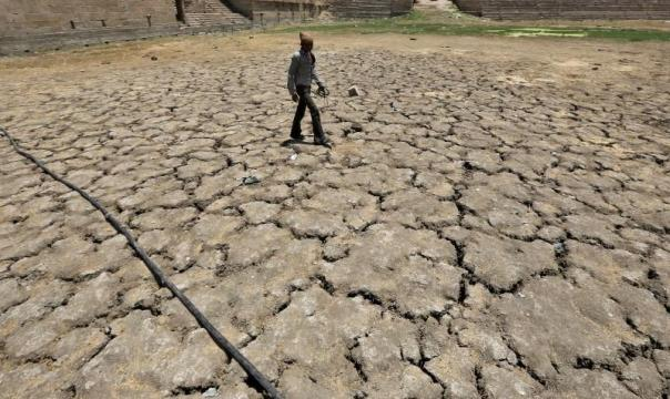 A man walks through a dried-up Sarkhej lake on a hot summer day in Ahmedabad